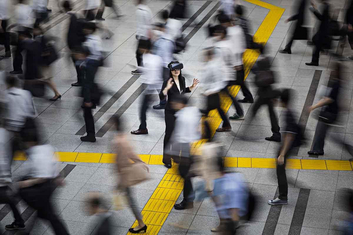 Japanese businesswoman using VR simulator glasses in the street