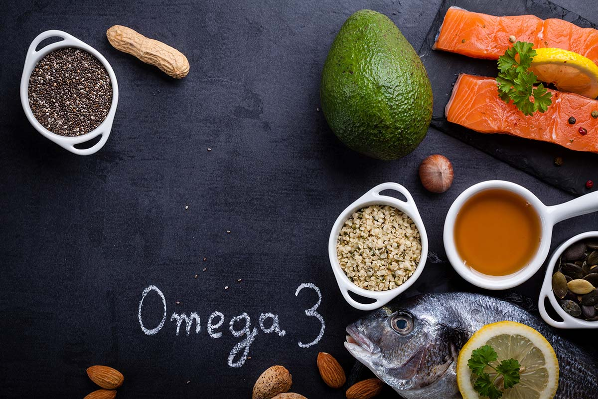 Black slate table with product rich in omega 3 and vitamin D. Written word omega 3 by white chalk.